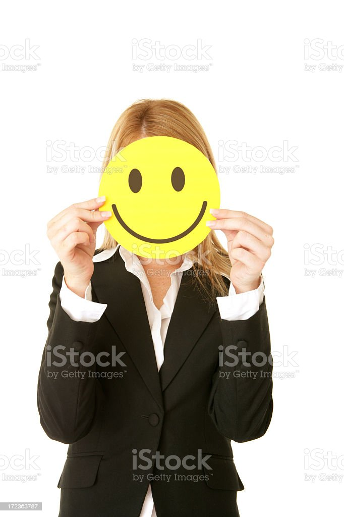Businesswoman holding happy face mask in front of face royalty-free stock photo
