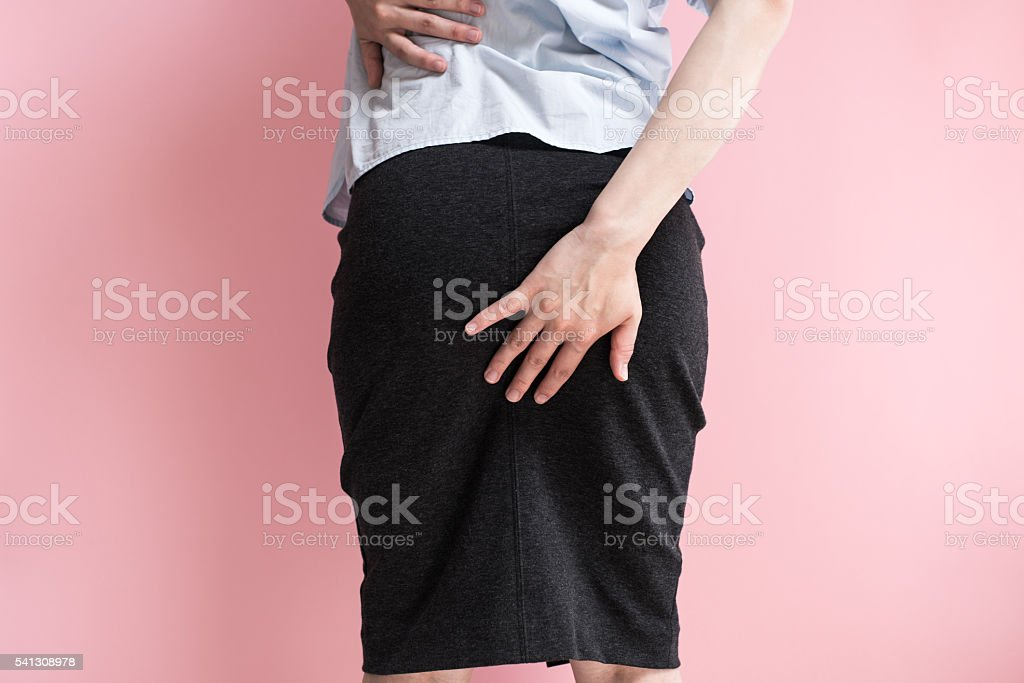 Businesswoman holding her bottom stock photo