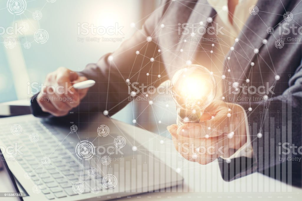 Businesswoman holding in his hand a burning lamp. stock photo