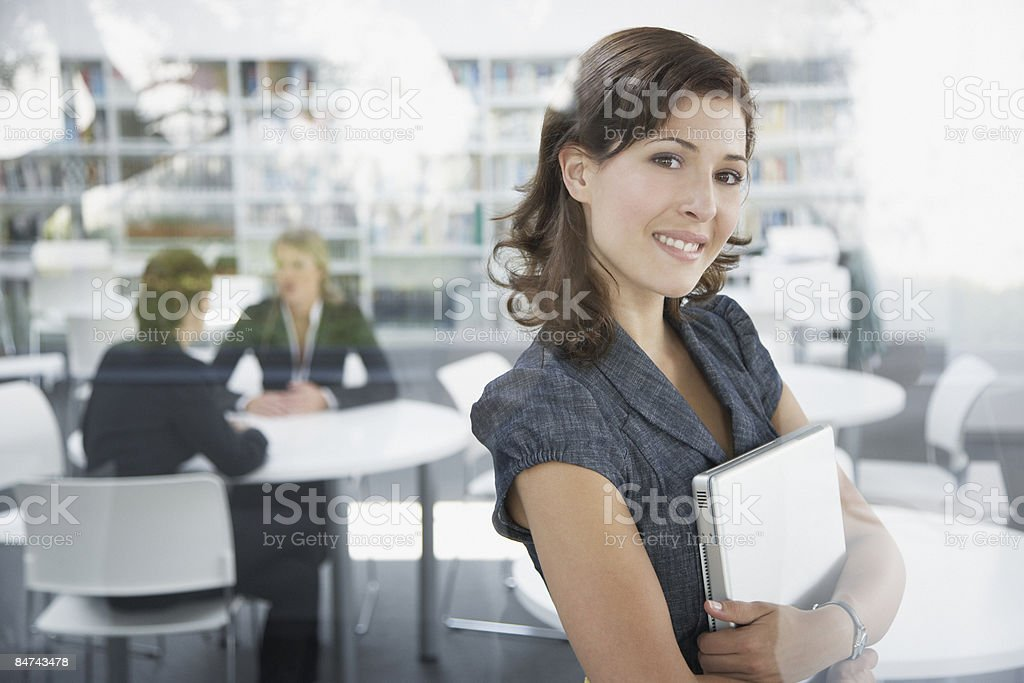 Businesswoman holding laptop in office royalty-free stock photo