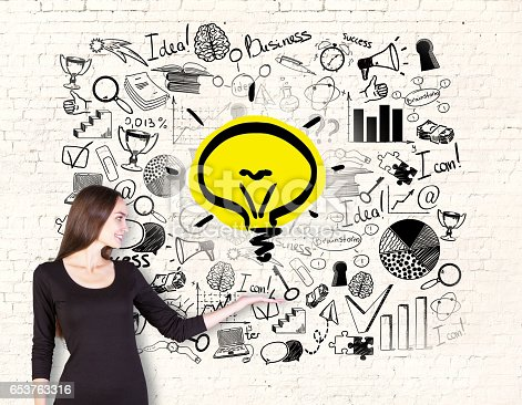 855515858 istock photo businesswoman holding lightbulb 653763316