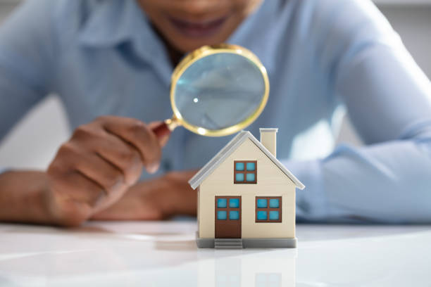 businesswoman holding magnifying glass over house model - esaminare foto e immagini stock