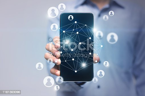 497982910 istock photo Businesswoman holding mobile phone with VR diagram of connection 1161363096