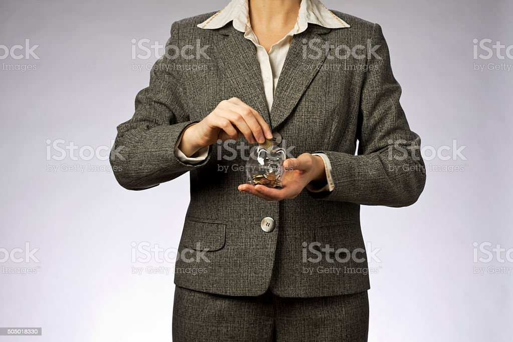 Businesswoman holding money box, putting euro coin into piggi bank stock photo