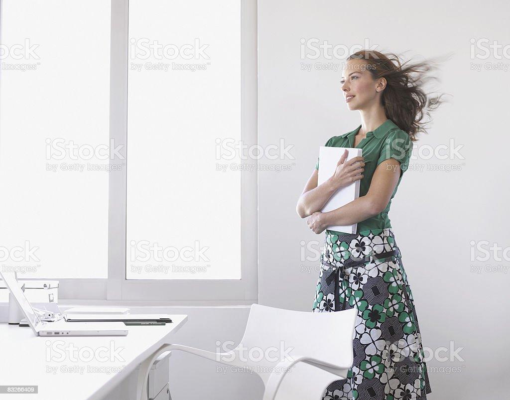 Businesswoman holding paperwork with wind blowing royaltyfri bildbanksbilder