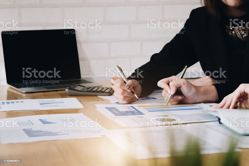 Businesswoman holding pens and holding graph paper are meeting to...