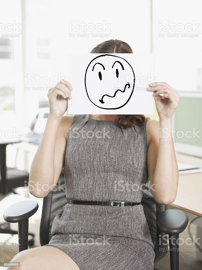 Businesswoman holding picture of frustrated face stock photo