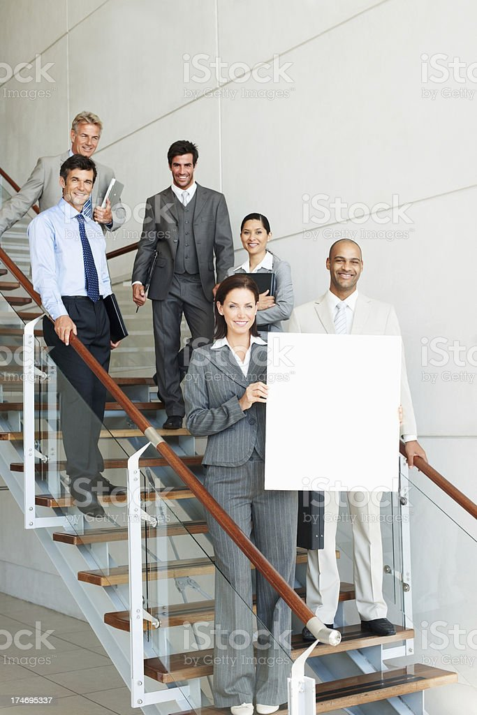 Businesswoman holding placard with colleagues standing in background royalty-free stock photo