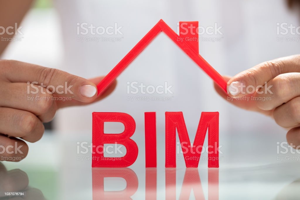 Businesswoman Holding Roof Over BIM stock photo