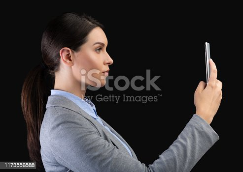 istock Businesswoman Holding Smartphone Using Face Recognition System Over Black Background 1173556588