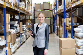 Cheerful young businesswoman holding digital tablet and standing in warehouse. Young blond woman working at distribution warehouse and wearing elegant suit. Industrial boss sincerely smiling and looking at camera. Logistic job in a modern storage compartment. Large distribution storage room in background with racks and shelfs full of packages, boxes, pallets, crates ready to be delivered. Logistics, freight, shipping, receiving.