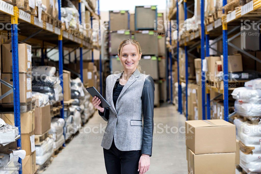 Businesswoman holding tablet and smiling in warehouse stock photo