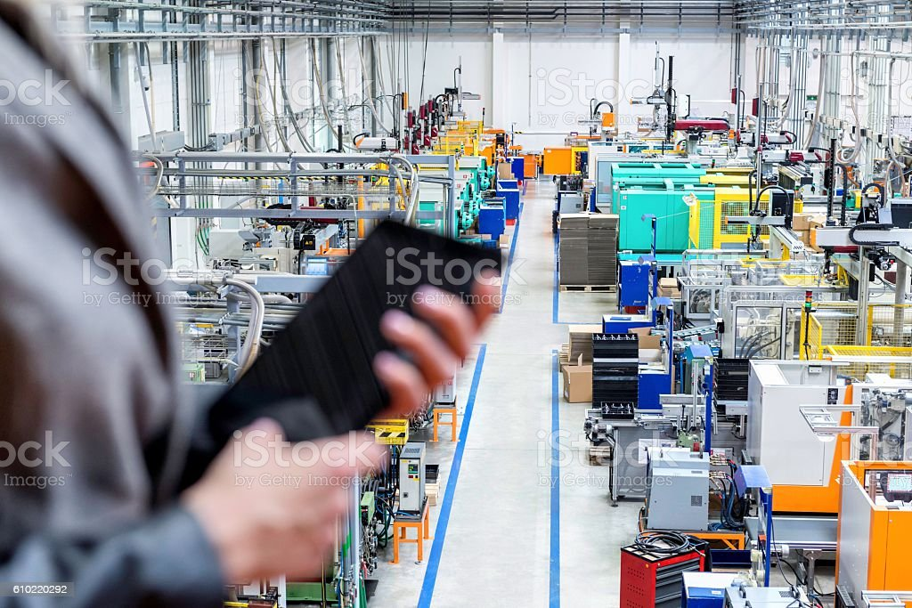 Businesswoman holding tablet, focus on robotic machines stock photo