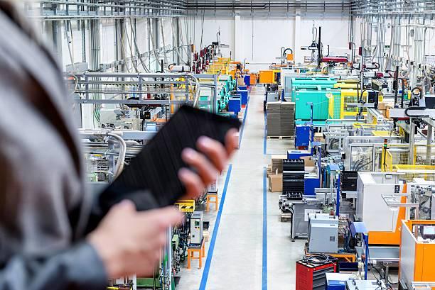 businesswoman holding tablet, focus on robotic machines - tablet mit displayinhalt stock-fotos und bilder