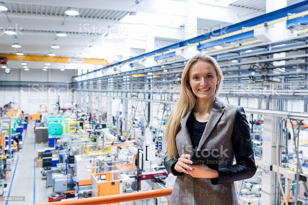 Businesswoman holding tablet on top of production line stock photo