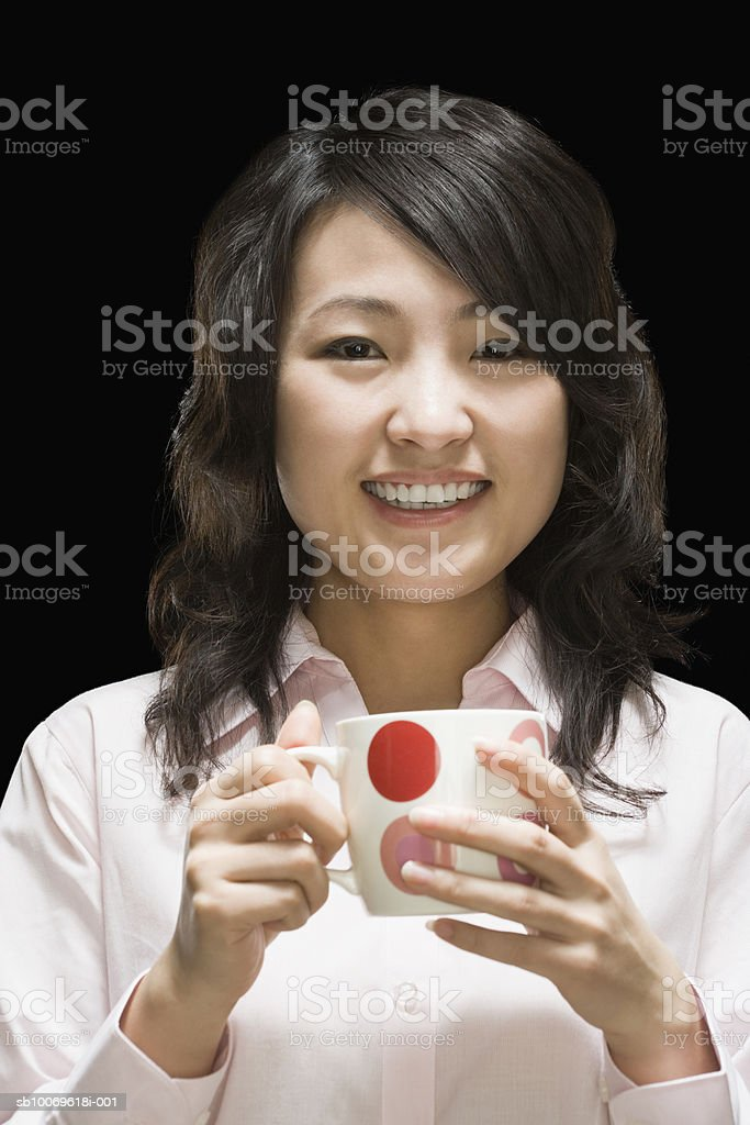 Businesswoman holding tea cup, smiling, portrait, close-up royalty-free stock photo