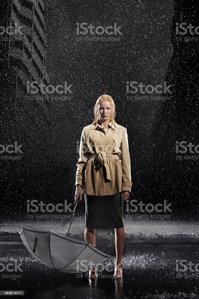 Businesswoman Holding Umbrella Upside Down In Rain stock photo