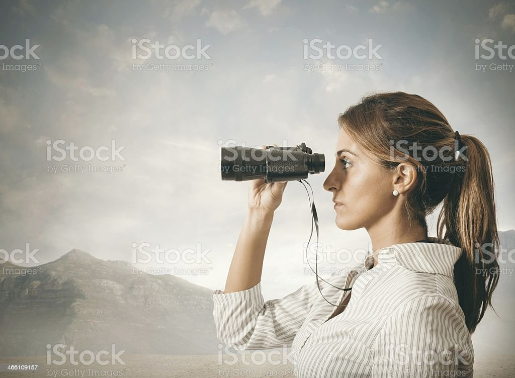 Businesswoman holding up binoculars in wilderness stock photo
