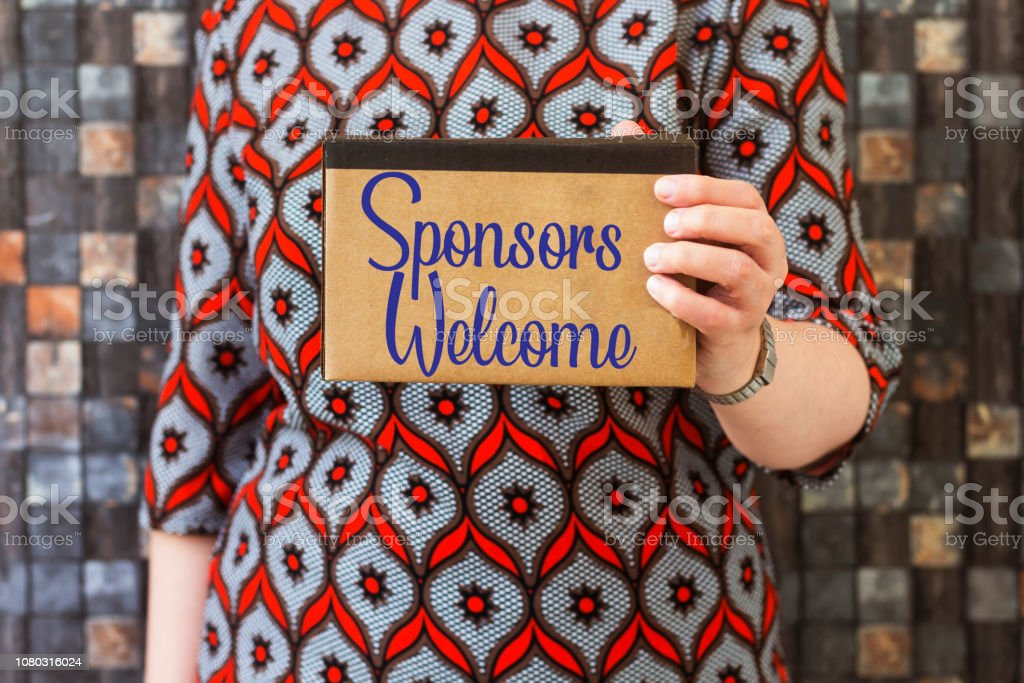 businesswoman holding white cardboard with writing showing Sponsors Welcome stock photo
