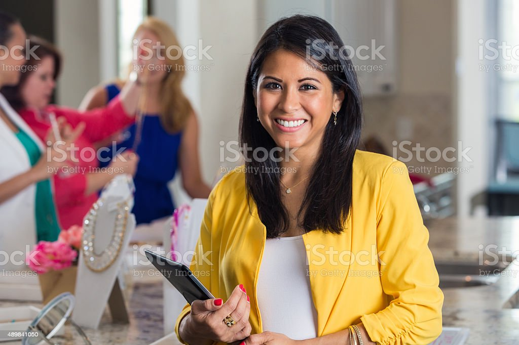 Businesswoman hosting direct sales home party with jewelry display stock photo
