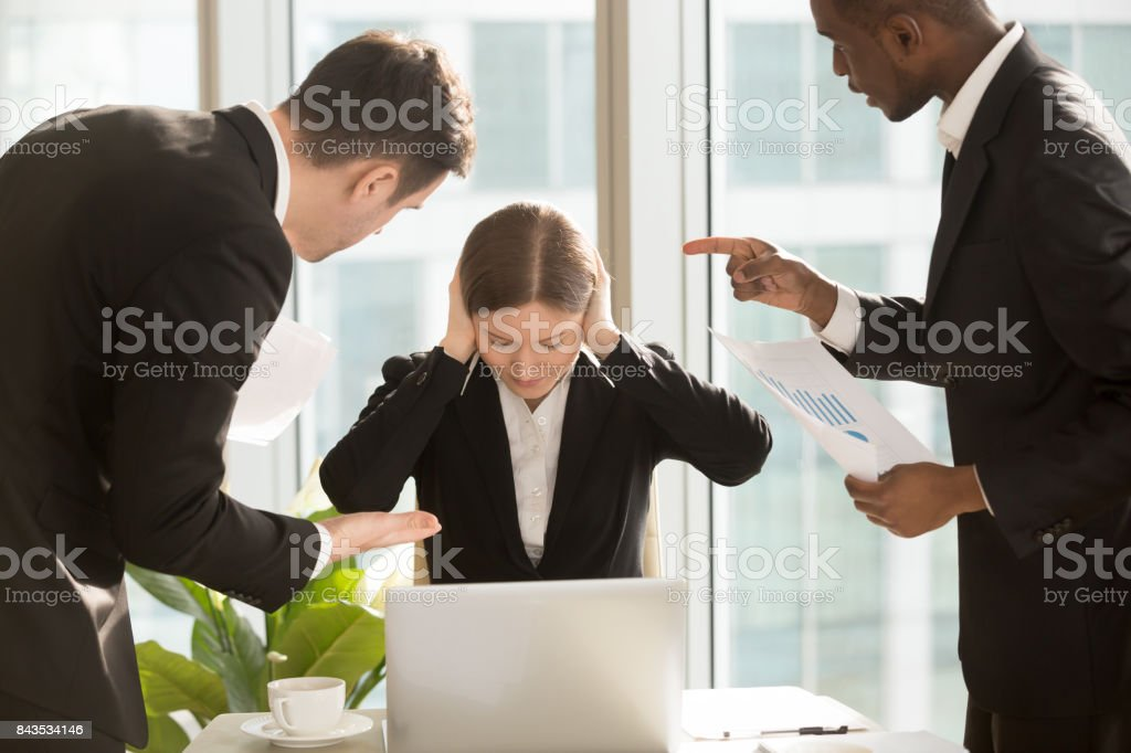 Businesswoman ignoring colleagues critical remarks stock photo