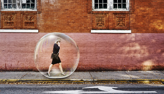 Businesswoman in a bubble for protection walking on a sidewalk using mobile phone in the city.