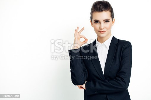 istock Businesswoman in black suit thumbs up isolated on white 913522058