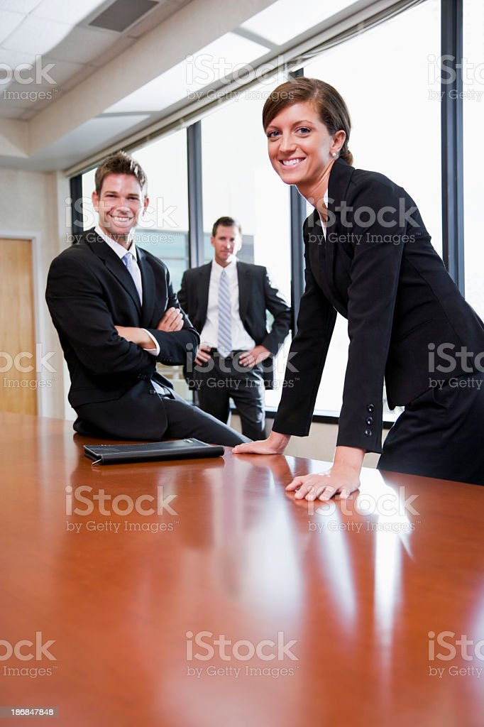 Businesswoman in boardroom with male co-workers royalty-free stock photo