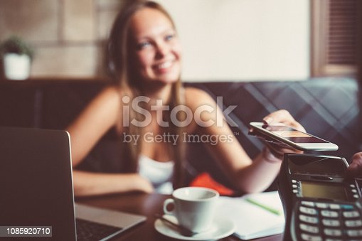 istock Businesswoman in cafe paying contactless with smartphone 1085920710