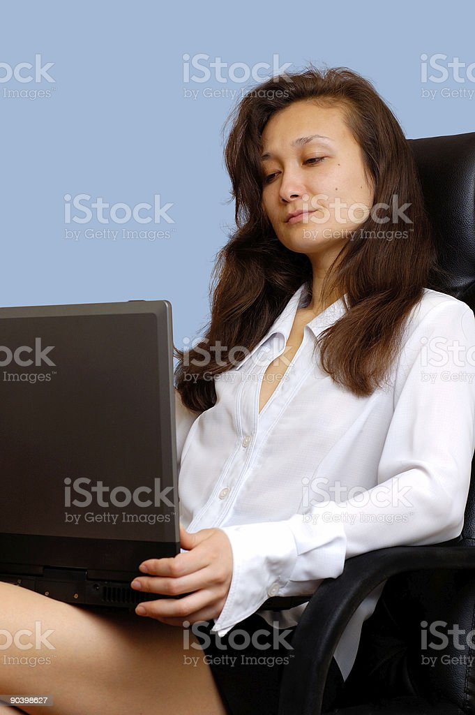 Businesswoman in chair working on laptop happy royalty-free stock photo