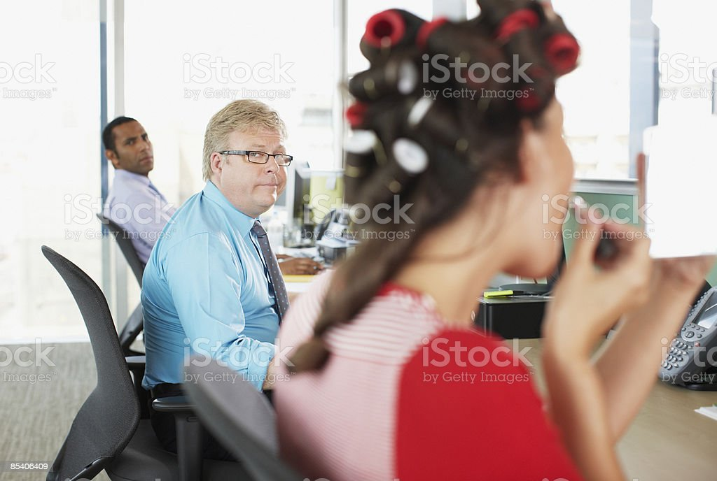 Businesswoman in curlers putting on lipstick in office royalty-free stock photo