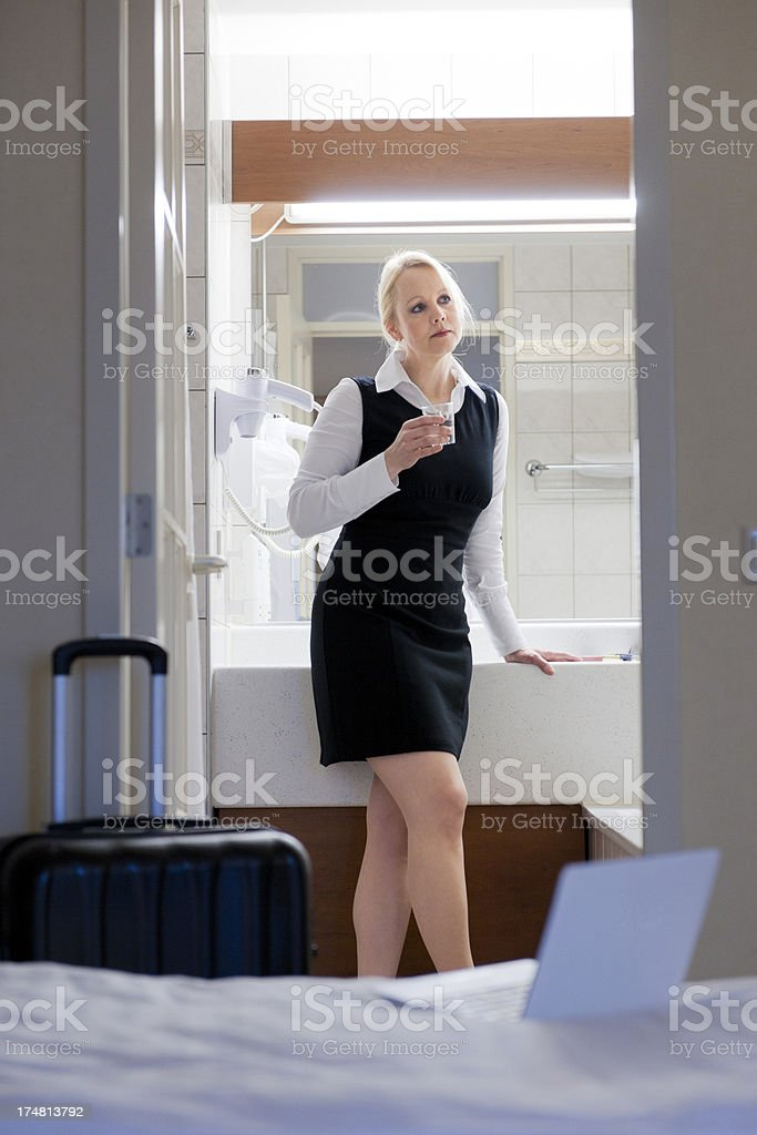 businesswoman in drinking water hotel bathroom stock photo