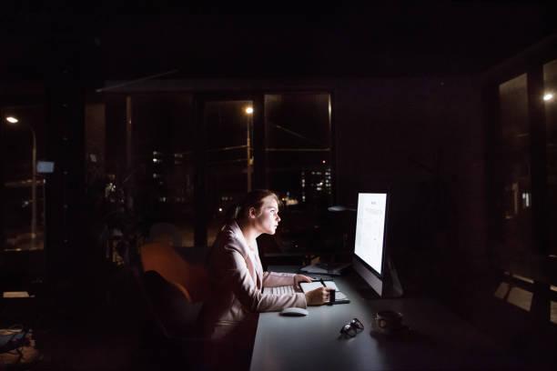empresaria frente a la pantalla de la computadora en la oficina por la noche. - trabajar hasta tarde fotografías e imágenes de stock