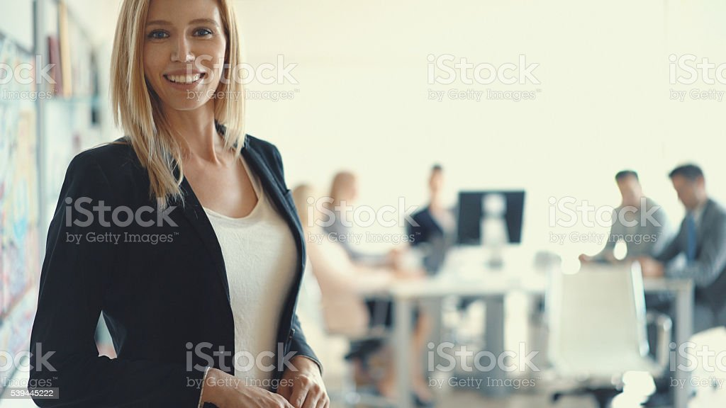 Businesswoman in front of her team. stock photo