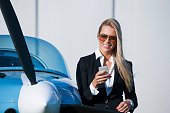 Young businesswoman,  in frontof  private jet airplane waiting for flight while speak on mobile phone. She is wearing sunglasses
