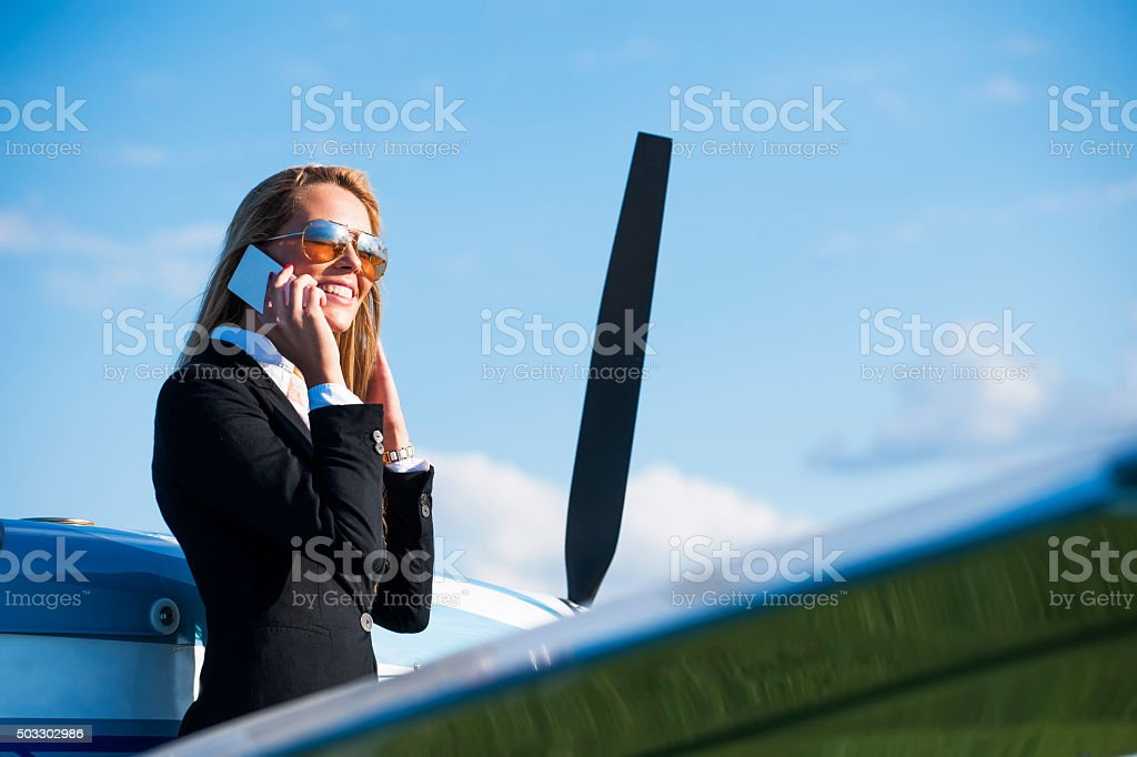 Businesswoman in front of private jet airplane stock photo