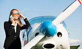 Young businesswoman,  in front of  private jet airplane, waiting for flight while speak on mobile phone. She is wearing sunglasses