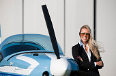 Young businesswoman,  in front of  private jet airplane waiting for flight . She is wearing suit and sunglasses