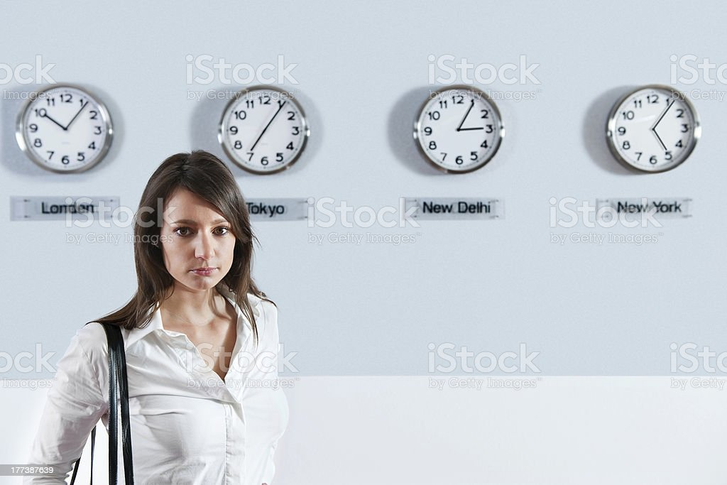 Businesswoman In Front Of World Time Zone Clocks stock photo