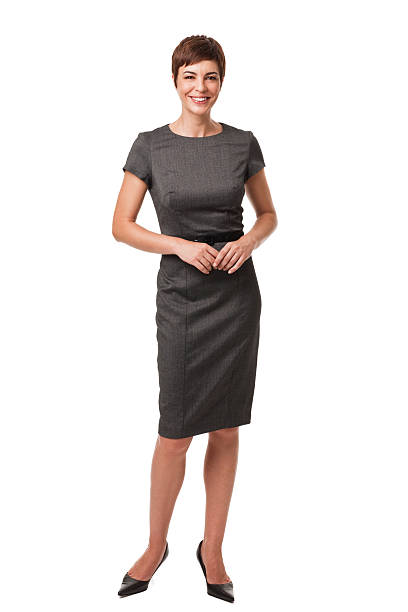 Businesswoman in Gray Dress Isolated on White Short haired businesswoman wearing a gray, belted dress. She is standing with her fingers clasped and is isolated on a white background. Vertical shot. dress stock pictures, royalty-free photos & images