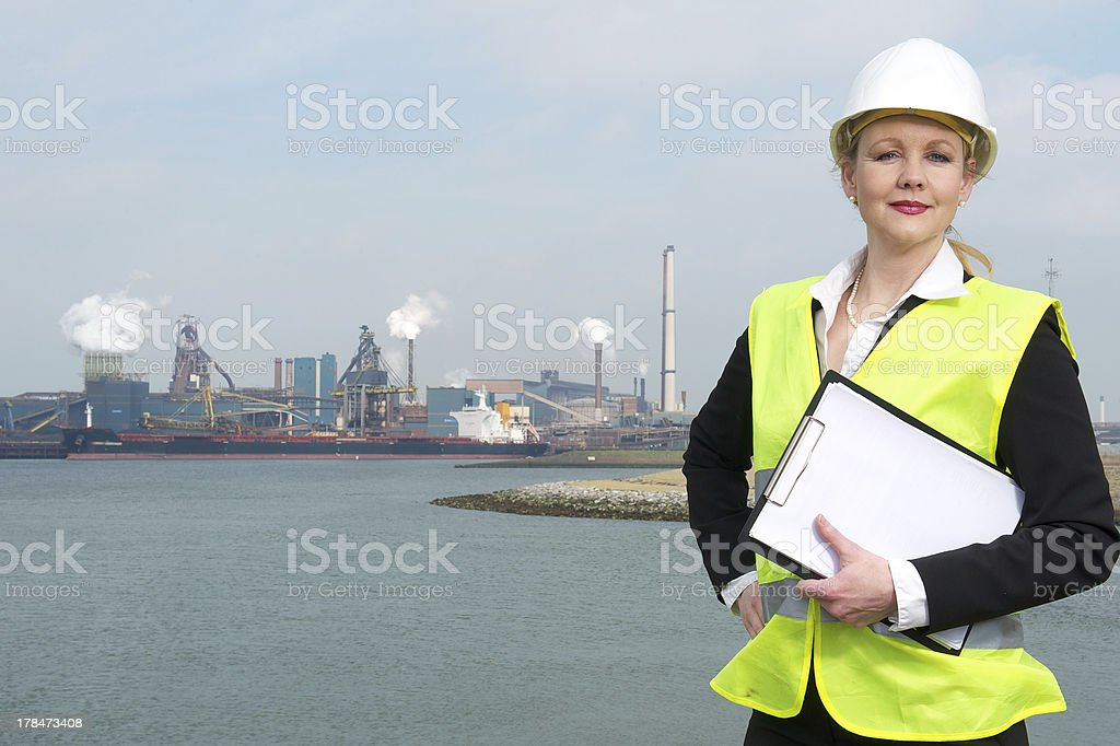Businesswoman in hardhat and safety vest holding a clipboard outdoors stock photo