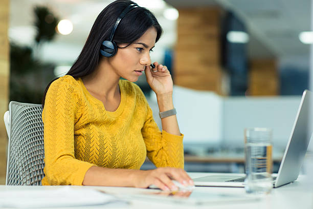 Businesswoman in headphones using laptop stock photo