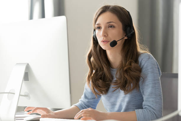 Businesswoman in headset call center agent consulting participating video conference Serious young businesswoman in wireless headset call center agent telemarketer consulting client participating business video conference talk help as customer care service support helpline in office service stock pictures, royalty-free photos & images