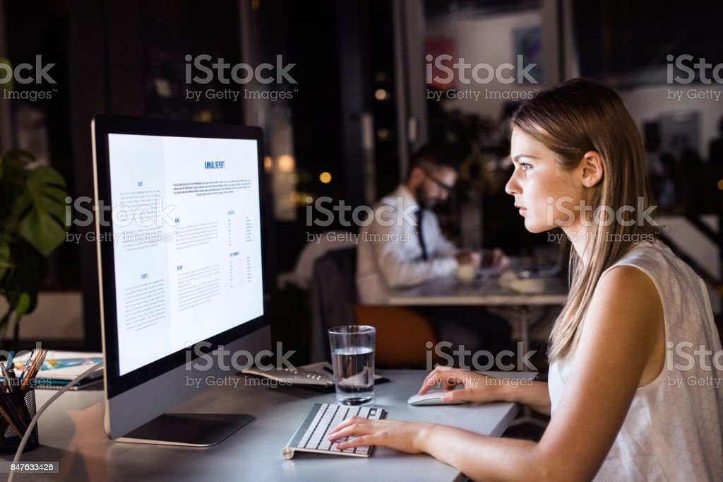 Businesswoman in her office at night working late stock photo