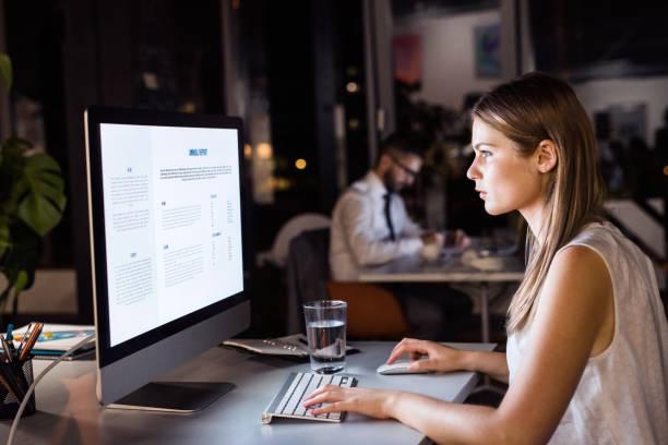 empresaria en su oficina de trabajo tarde noche - trabajar hasta tarde fotografías e imágenes de stock