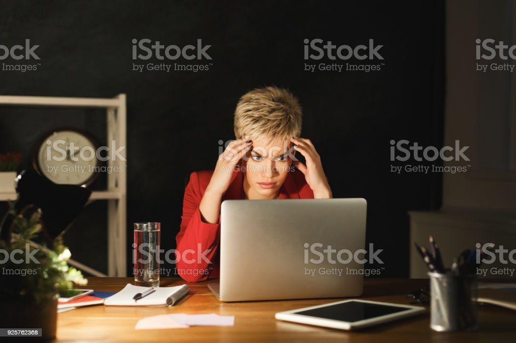 Tired businesswoman working in office late at night. Portrait of...
