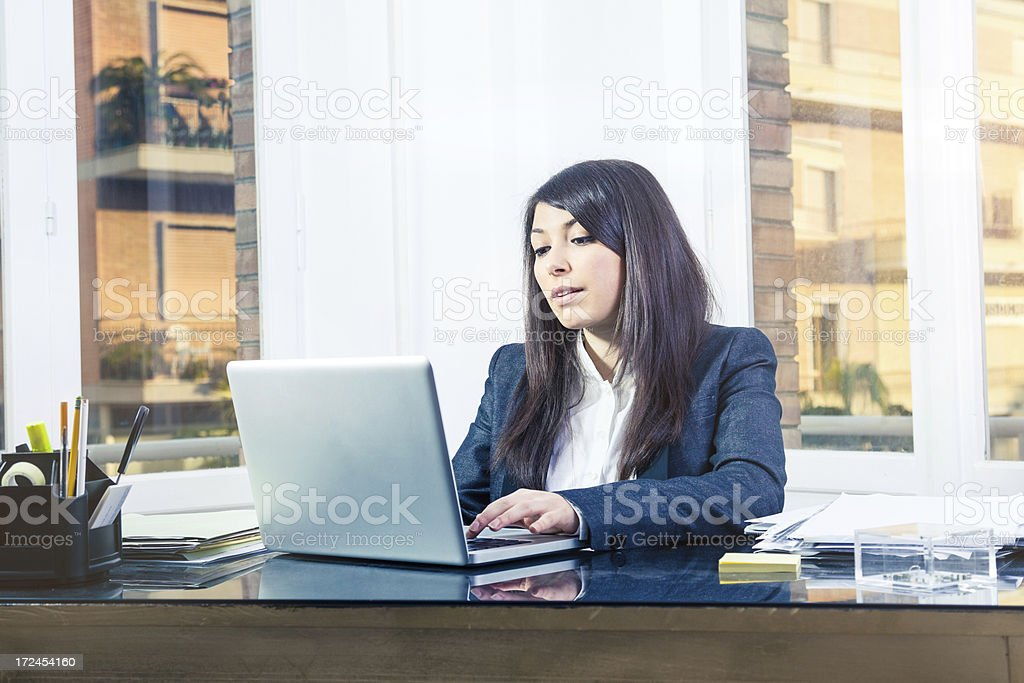 Businesswoman in her office working on laptop royalty-free stock photo