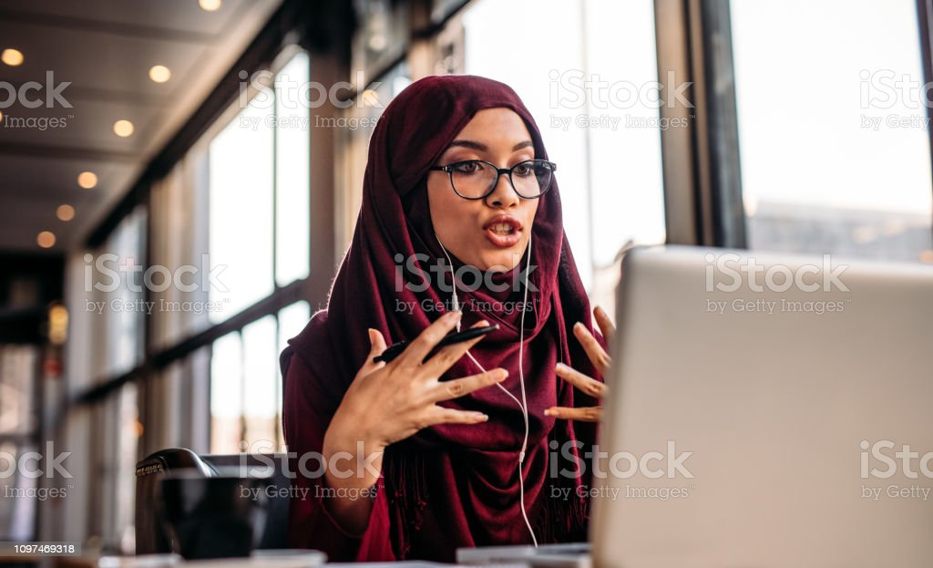 Businesswoman in hijab having a video chat on laptop - Foto stock royalty-free di Abbigliamento modesto