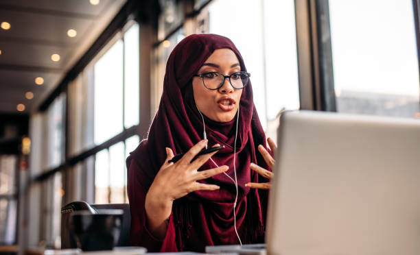 businesswoman in hijab having a video chat on laptop - hijab foto e immagini stock