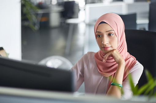 Businesswoman in hijab working at computer desk